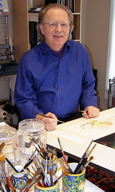 photo of watercolorist, Laurin McCracken in his studio with paper and paintbrushes around him.