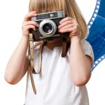 child with camera and film background
